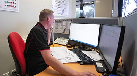 staff at a desk on the phone looking at pc